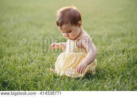 Funny Baby Kid. Cute Adorable Baby Girl In Yellow Dress Sitting On Grass In Park Outdoors. Funny Chi