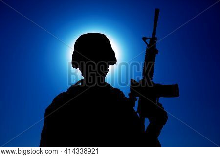 Silhouette Of Army Soldier Standing With Service Rifle In Hand On Background Of Night Sky With Moon.