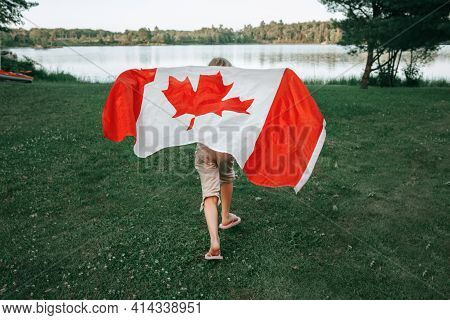 Girl Wrapped In Large Canadian Flag By Muskoka Lake In Nature. Canada Day Celebration Outdoors. Kid