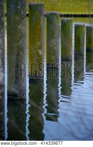 Close Up Of Water Reflection Of Columns Installed In A Lake In France