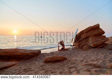 Yogi Woman Practicing Yoga On Seashore. One Legged King Pigeon Exercise. Eka Pada Rajakapotasana Pos