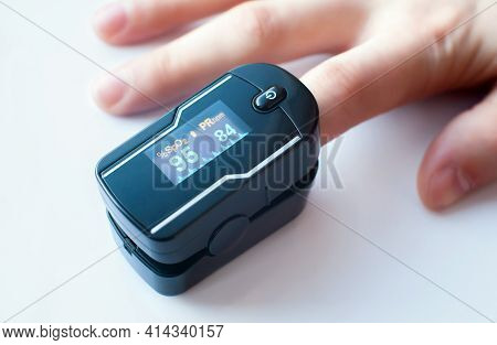 Pulse Oximeter On The Index Finger On A White Background. Blood Oxygen And Pulse Measurements