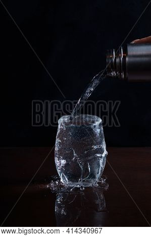 Water Is Poured From A Bottle Into A Glass And Spills Past Over The Edge, Blurred Background