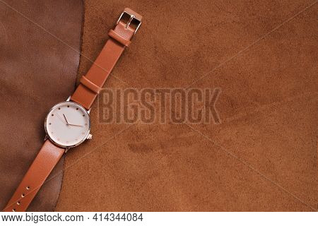 Watch With A Brown Leather Strap On A Brown Genuine Leather Background.genuine Leather Accessories.
