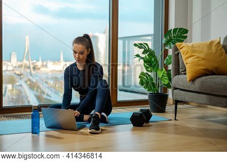Slender brunette in green jumpsuit searches videos on laptop sitting on floor near panoramic window and green pot plant in lodge