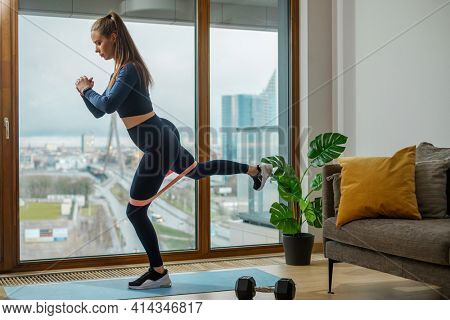 Slender brunette in green tracksuit practices exercises with stretch strap near panoramic window with view on street on balcony