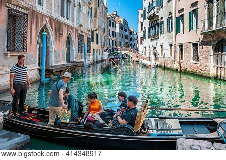 Venice, Italy. 04 September 2018. View Of The Canal And The Venetian Gondolas Carrying Asian Tourist