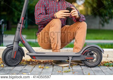 Anonymous Young Man Wearing Shirt Sitting On Curb Next To His Electric Scooter, Holding Mobile Smart