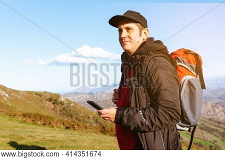 Hiker Using The Gps Of His Smartphone To Guide Him On His Route Through The Mountains. Person In Nat