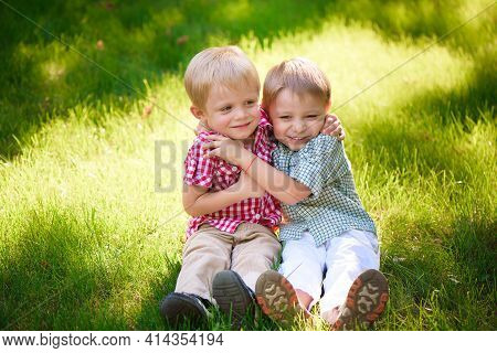Portrait Of Two Boys Embracing And Laughing Outdoors