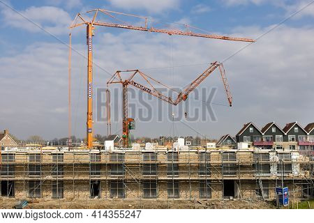 Urk, The Netherlands - March 25, 2021: Big Mobile Tower Cranes Unfolding At Construction Site Apartm