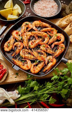 Roasted tiger prawns on iron grilling pan with fresh persley, lemon, chilli and bread