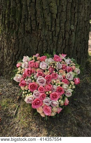 A Sympathy Flower Arrangement In A Heart Shape, Pink And Purple Roses