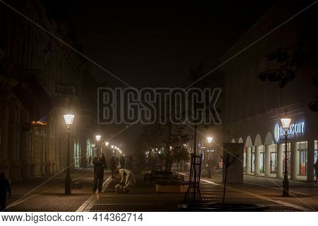 Subotica, Serbia - November 18, 2020 People Walking At Night During A Cold Autumn Evening On The Ped