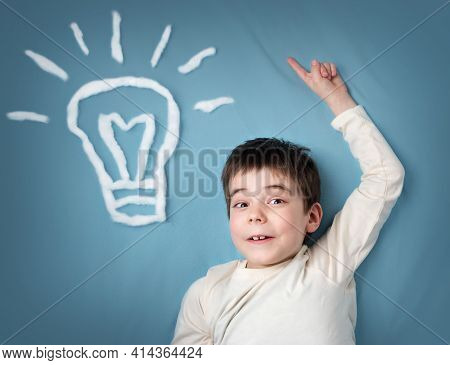 Seven Years Old Boy With A Bulb On Blue Background. Child With An Idea