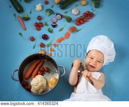 Baby Boy In Chef Hat With Cooking Pan And Raw Vegetables