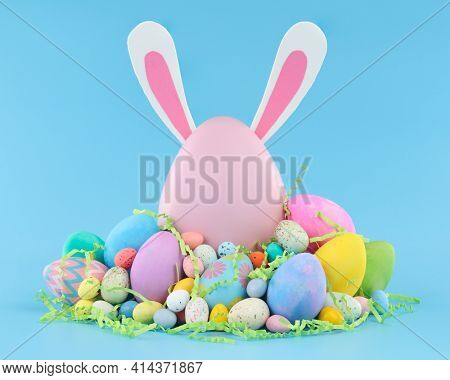 Large pink Easter egg with bunny ears surrounded by a pile of colorful Easter eggs and candy.