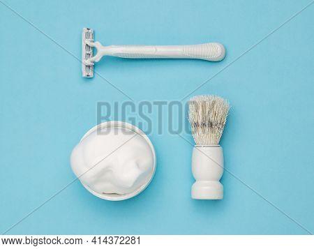 A White Razor, A White Shaving Brush, And A White Bowl Of Shaving Foam On A Blue Background. Set For