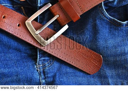 A Top View Image Of A Brown Leather Belt With Metal Buckle On A Pair Of Blue Jeans.