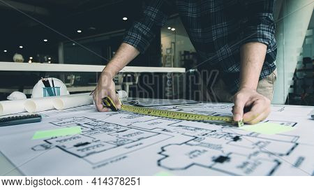 Young man with a laptop plotting a system of building structures in blueprints, Architects or engine