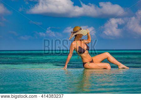 Woman Relaxing In Tropical Resort Hotel Pool In Straw Hat And Black Bikini. Vacation Girl Sexy Tan B