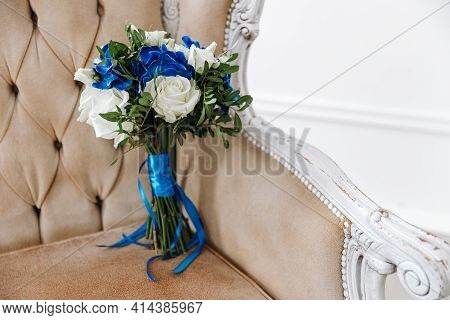 A Wedding Bouquet Of White Roses Lies On A Designer Armchair, Blue Ribbons. Floral Decoration For Th