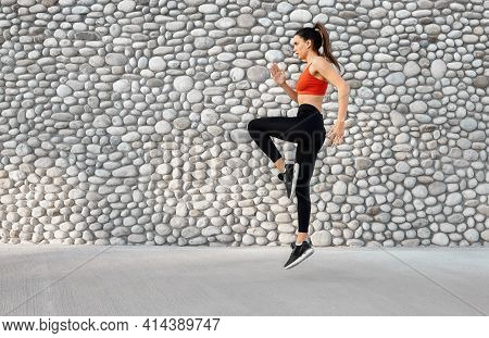 Young Fit Woman Doing Dynamic Action Jump Pose Next To Grey Stone Wall. Interval And Endurance Train