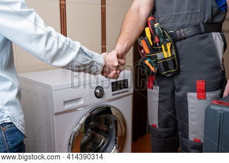 Close-up Of A Repairman Shaking Hands With A Female Customer. Male Repairman For Washing Machine Rep