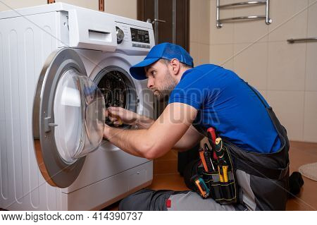 Working Man Plumber Repairs A Washing Machine In Home. Washing Machine Installation Or Repair. Plumb