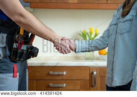 Close Up Of Plumber And Client Shaking Hands In Kitchen. Repairman Shaking Hands With Woman
