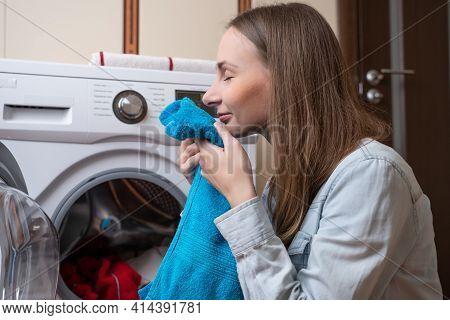 Young Woman Putting Laundry Into Washing Machine. Woman Washing Laundry Using Modern Automatic Machi