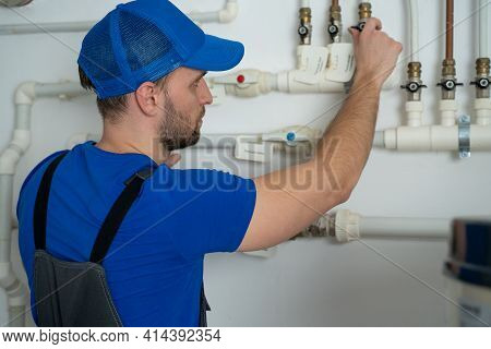 Uniformed Plumber Is At Work - Closing And Opening The Taps