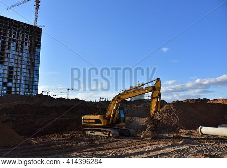 Excavator Dig Trench At Construction Site. Digging The Pit Foundation. Laying Concrete Sewer Wells A