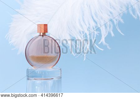 Unbranded Round Perfume Bottle On Glass Podium And Large White Ostrich Feather On Blue Background. T