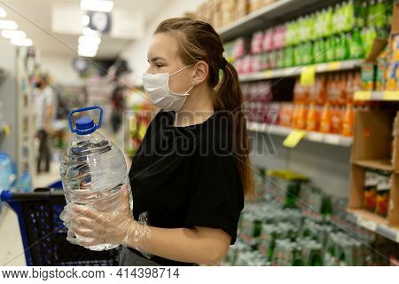 Woman Wearing Face Mask And Gloves Buying In Supermarket,smiling, Holding Water Botle. Panic Shoppin