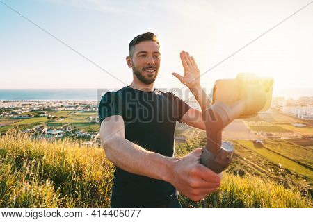 Young Man Blogger Recording Video Blog Or Live Streaming With Smartphone And Gimbal Outdoors. Social