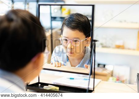 An Asian Boy Tries On Eyeglasses In An Eyeglass Shop. Kids Looked At Himself In The Mirror. Select F
