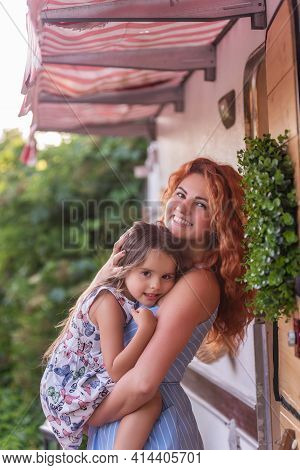A Beautiful Red-haired Young Mother Gently Holds, Hugs Little Daughter In Arms Near House With Trail