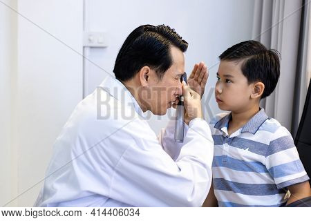 An Asian Male Doctor Uses An Ophthalmoscope To Examine The Boy's Eyes. The Ophthalmologist Examines