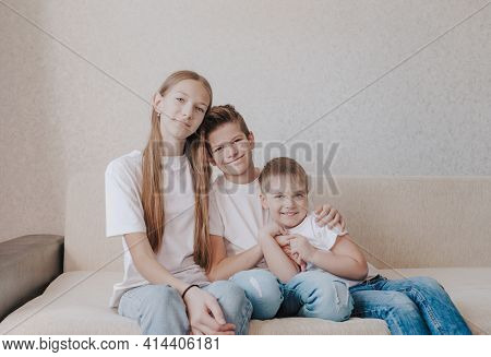 Three Children, A Girl And Two Boys In White T-shirts And Blue Jeans, Sit Hugging Each Other On The
