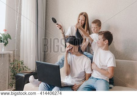 An Irritated Mother Sits On The Couch And Works At Home On A Laptop, Active Children Play With Their