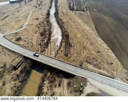 Miercurea Ciuc, Romania- 27 March 2021: Passing Car On The Bridge Over The Dirty Olt River.