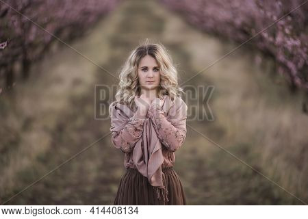 Young Beautiful Curly-haired Blonde Woman In Brown Pleated Skirt, Pink Blouse, Covered Shoulders Wit