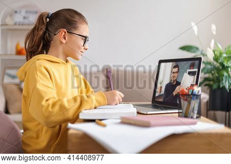 School Girl Having Video Conference With Online Teacher On Laptop In Living Room At Home. Homeschool