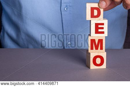 A Man In A Blue Shirt Composes The Word Demo From Wooden Cubes Vertically