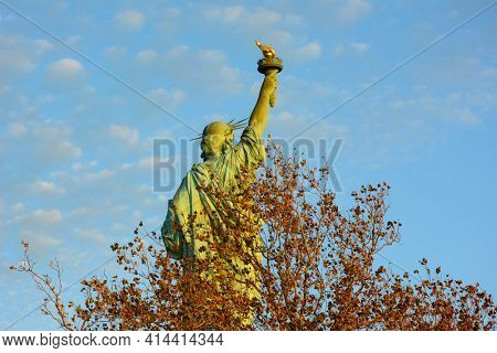 Closeup of the Statue of Liberty from behind with autumn trees, blue sky and clouds.