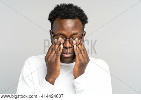 Sleepy African American Man Wear Glasses Rubbing His Eyes, Feels Tired After Work On Laptop Computer