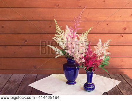 Red, White And Pink Beautiful Astilbe Flowers In Blue Vases On Wooden Table. Selective Focus. View W