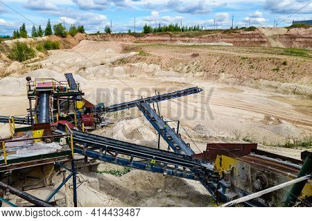 Stone Crush Machinery & Its Elements In Open Pit Mine. Dumps Of Materials & Loading Area Are On Back