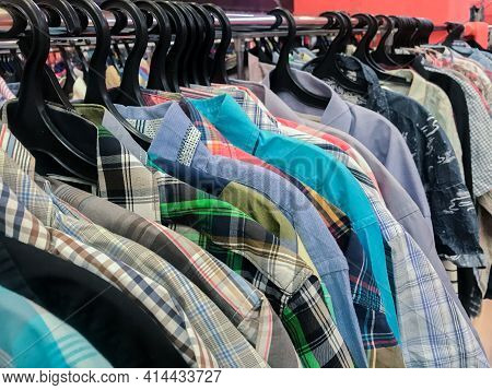Row Of Huge Numbers Of Colorful Shirts On Hangers In Second Hand Store. The Concept Of Cheap Shoppin